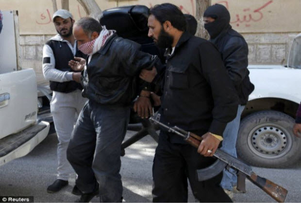Islamist Syrian rebel group Jabhat al-Nusra hold a detainee as they transport him in Raqqa province